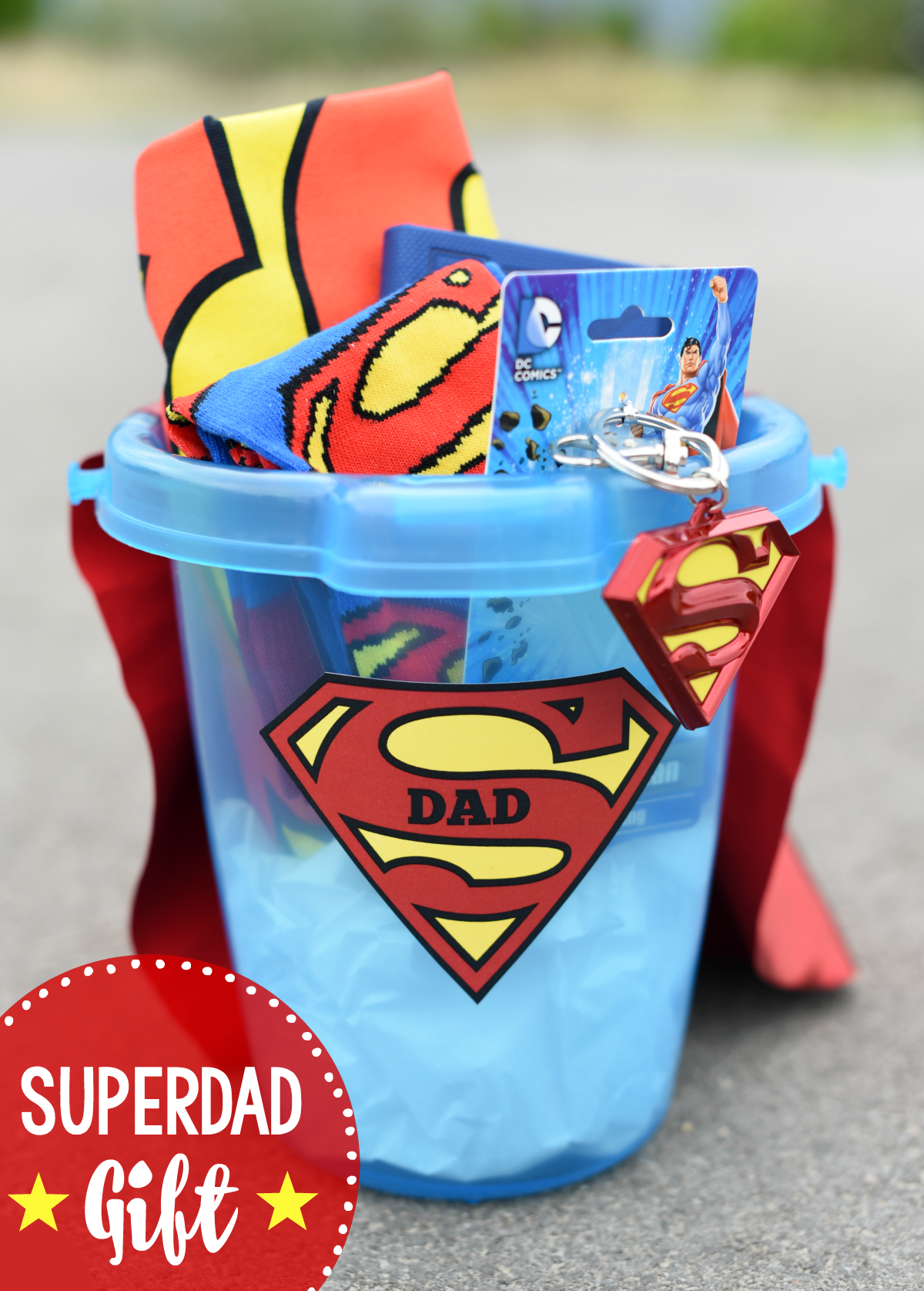 Superhero Fathers Day Gift Basket-Fill a basket (or bucket) with Superman themed items, add a cute Superdad tag and a cape to the back of the bucket and you have a great Superdad gift! #fathersdaygifts #fathersday #fathersdayideas #dad #dadgifts #gifts #giftideas #giftsfordad #superman #superdad #superhero