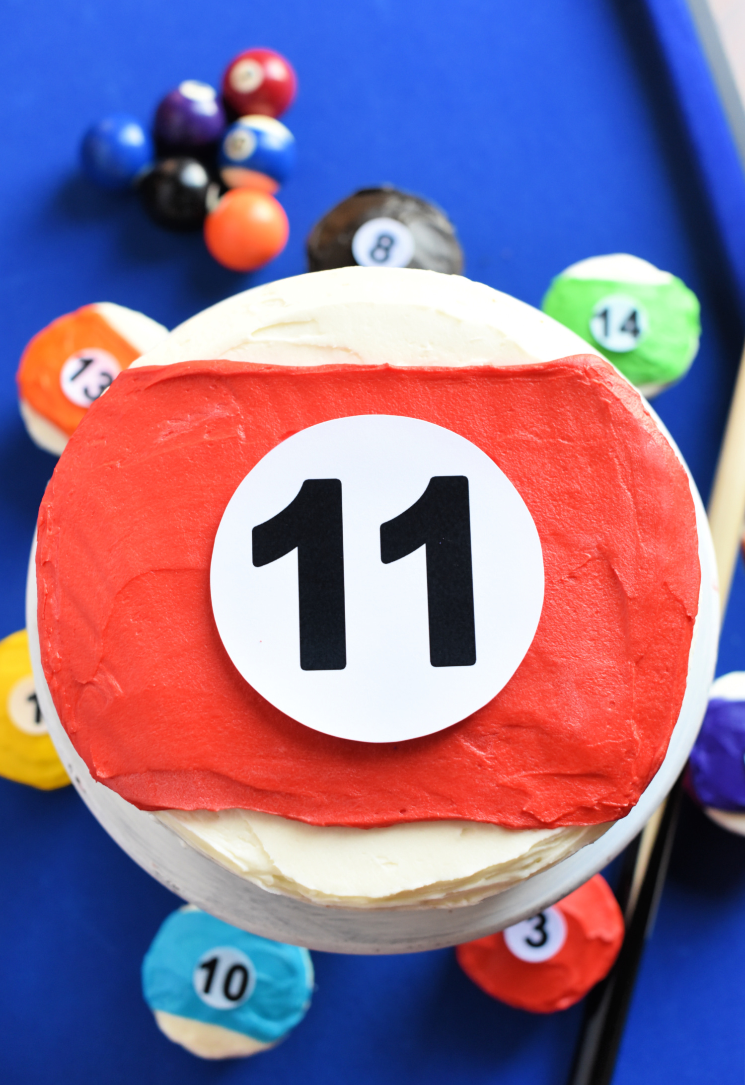 Fun Pool Table Cake Idea-If you've got a little one that loves to play billiards, this fun pool ball cake is perfect. Make the main cake the number of the age they are turning and then cupcakes of all the other pool balls. Easy to make-you can do it! #cakes #cake #dessert #birthdaycake #billiards #birthdayparty